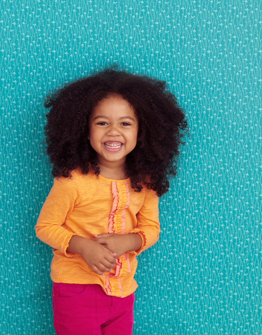 African-American girl laughing in front of a patterned wall for Parents magazine