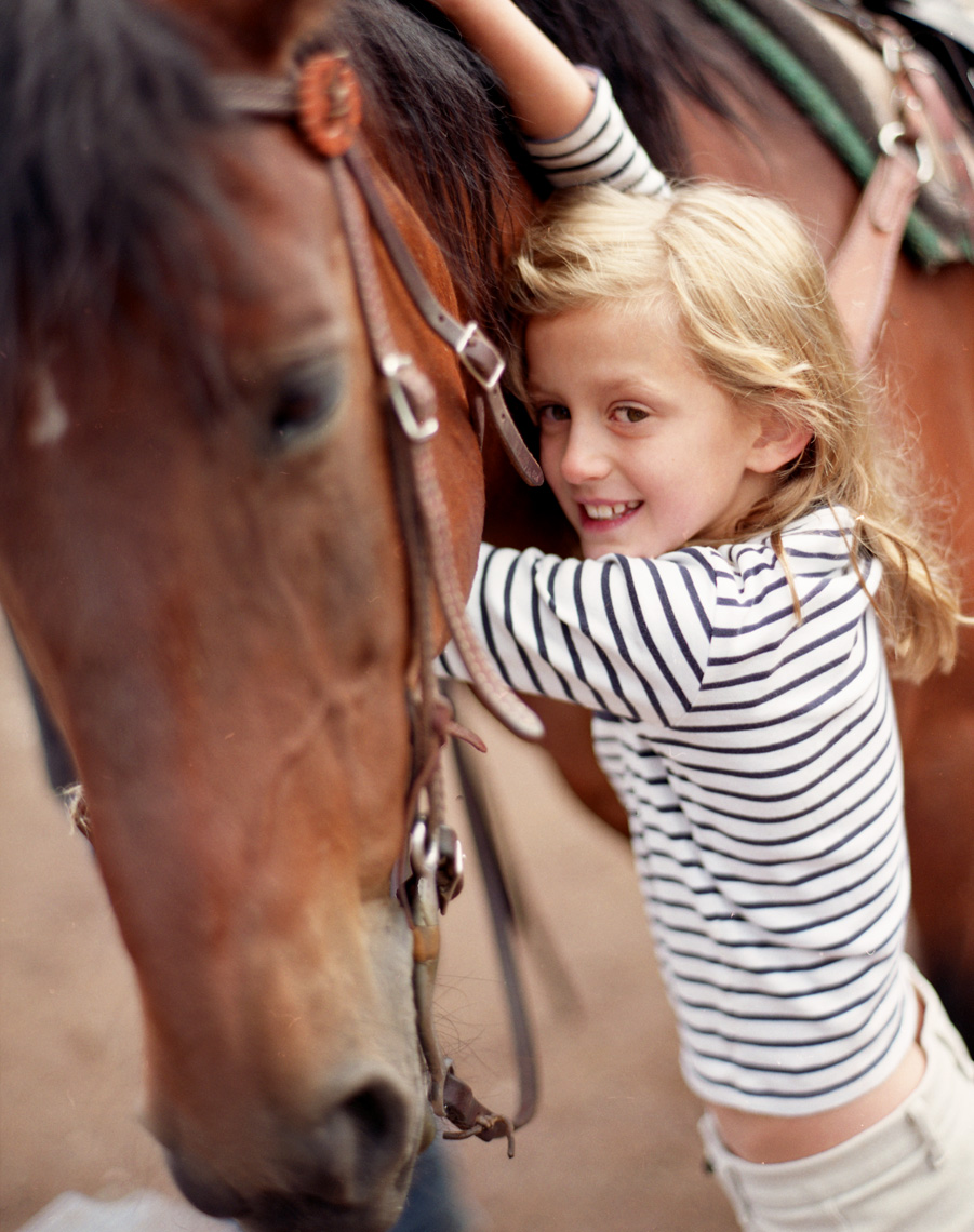girl hugging horse in striped shirt