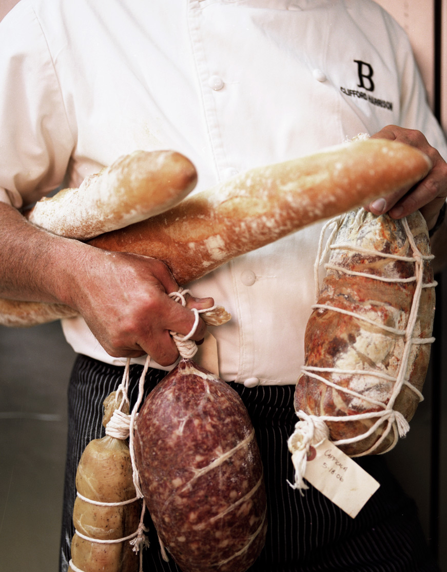 chef holding armful of charcuterie shot for Travel & Leisure