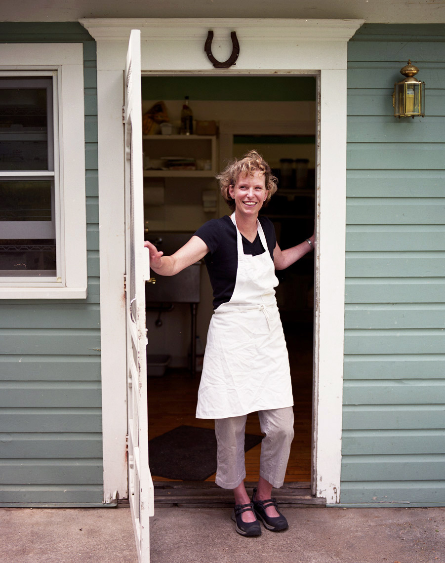 cafe worker with apron at back door of house