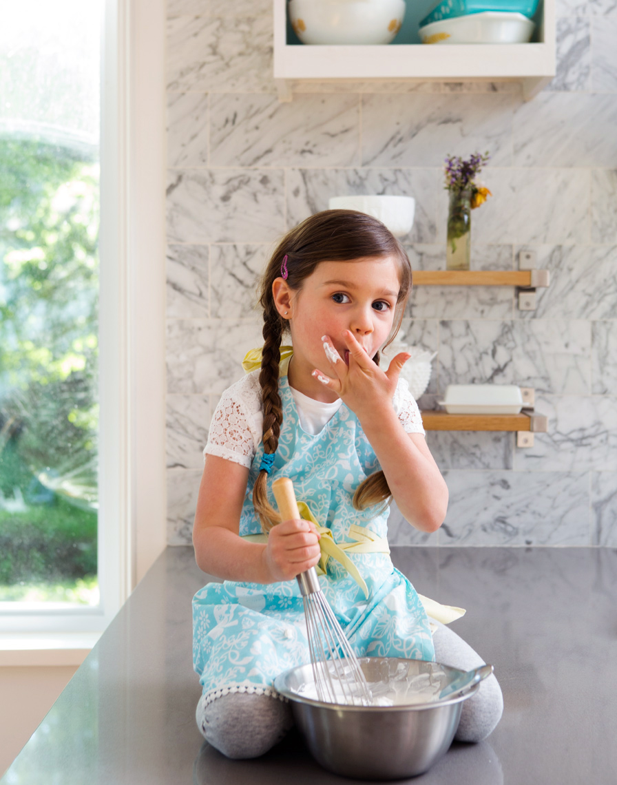 Girl with whipped cream  sitting on kitchen counter