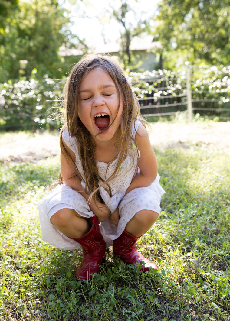 Young girl with vintage cowboy boots screaming powerful scream