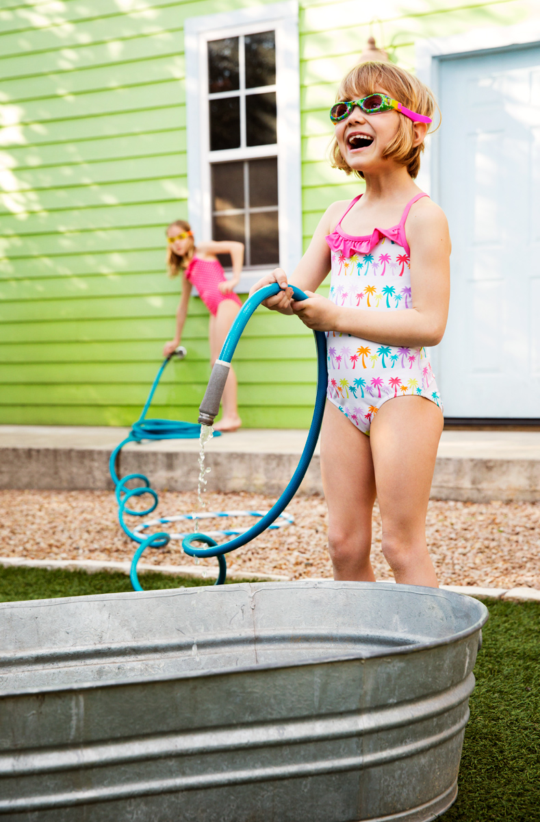 Girl in bathing suit backyard with hose and sister