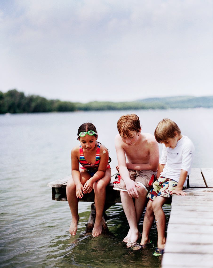 three kids on dock looking at water family summer travel