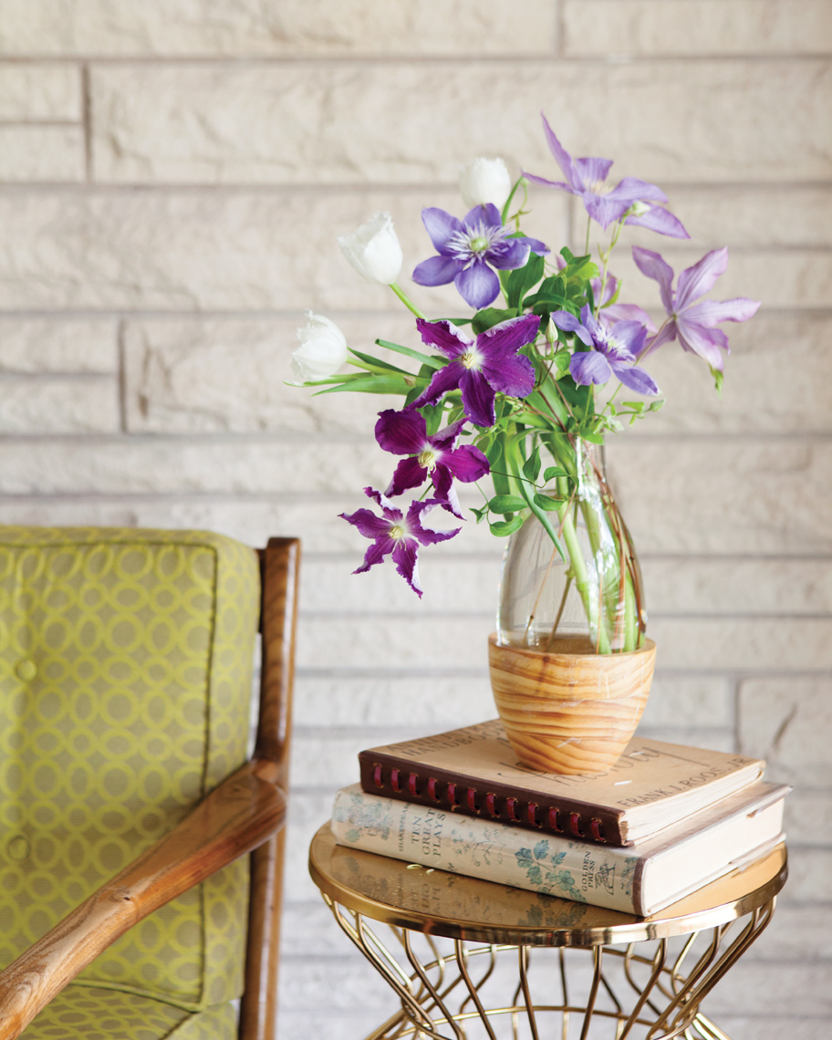 Camille Styles Entertaining living with spring flowers by modern chair