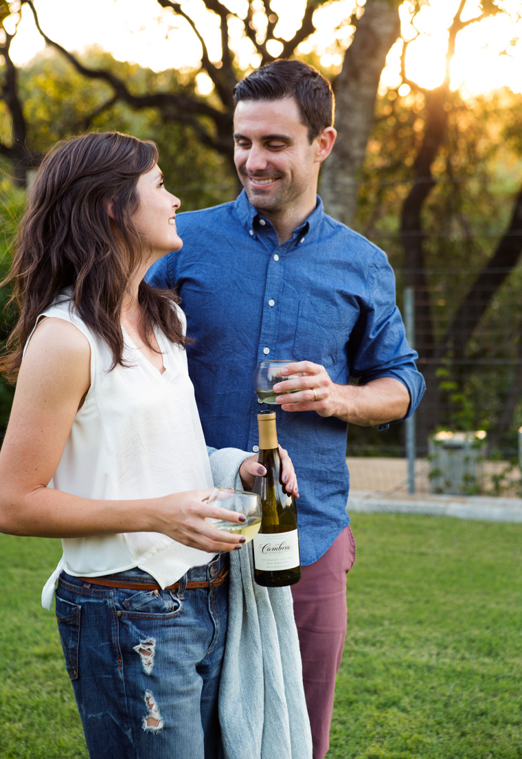 Couple with bottle of wine at picnic.