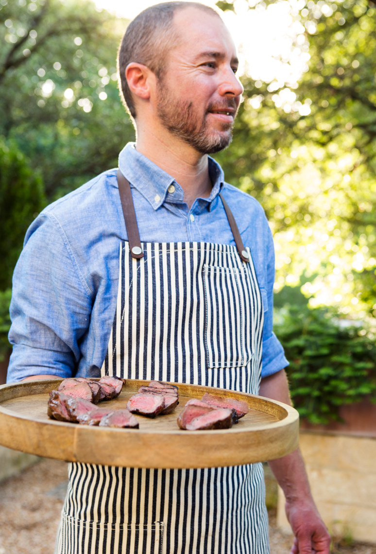 Camille Styles blog chef with platter of grilled steaks outdoors