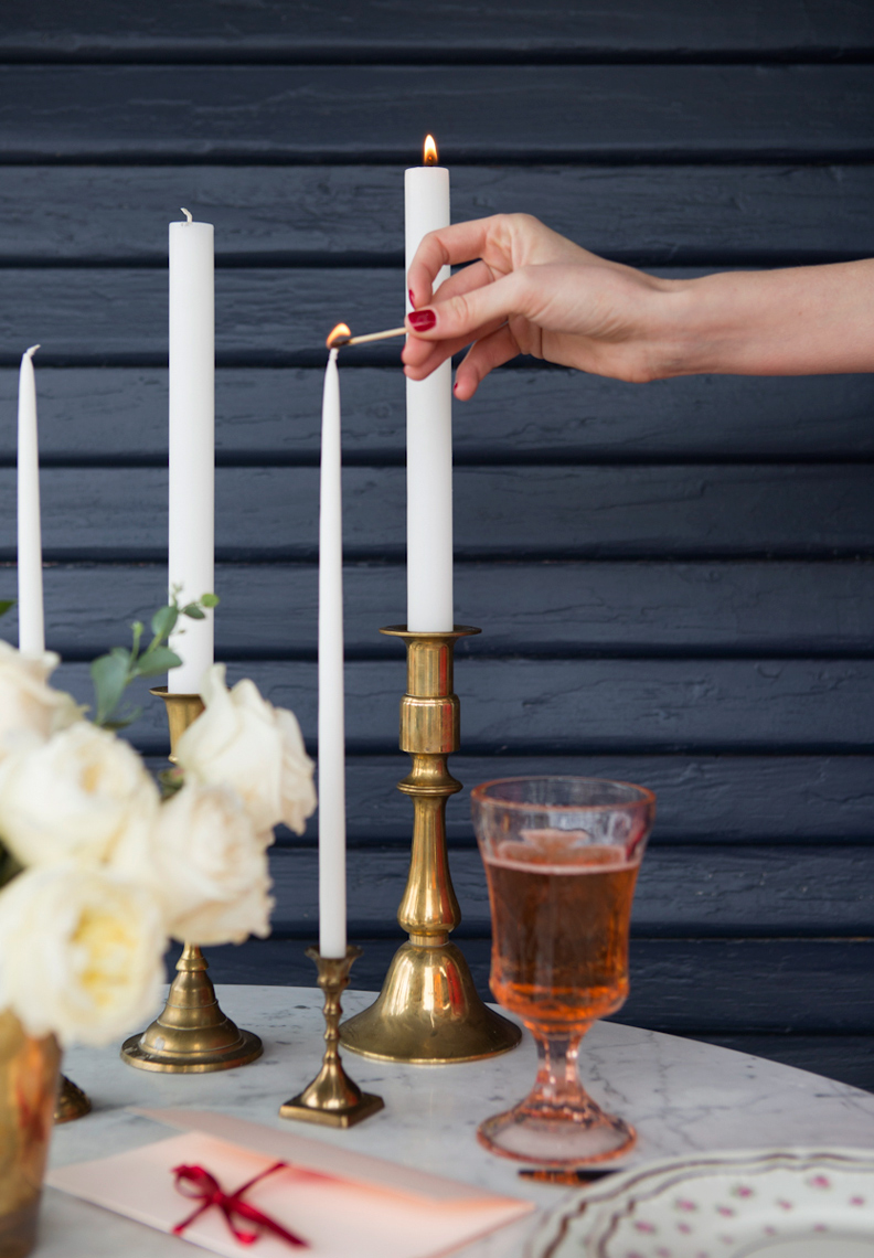 Camille Styles blog lighting candles for a romantic dinner brass candles