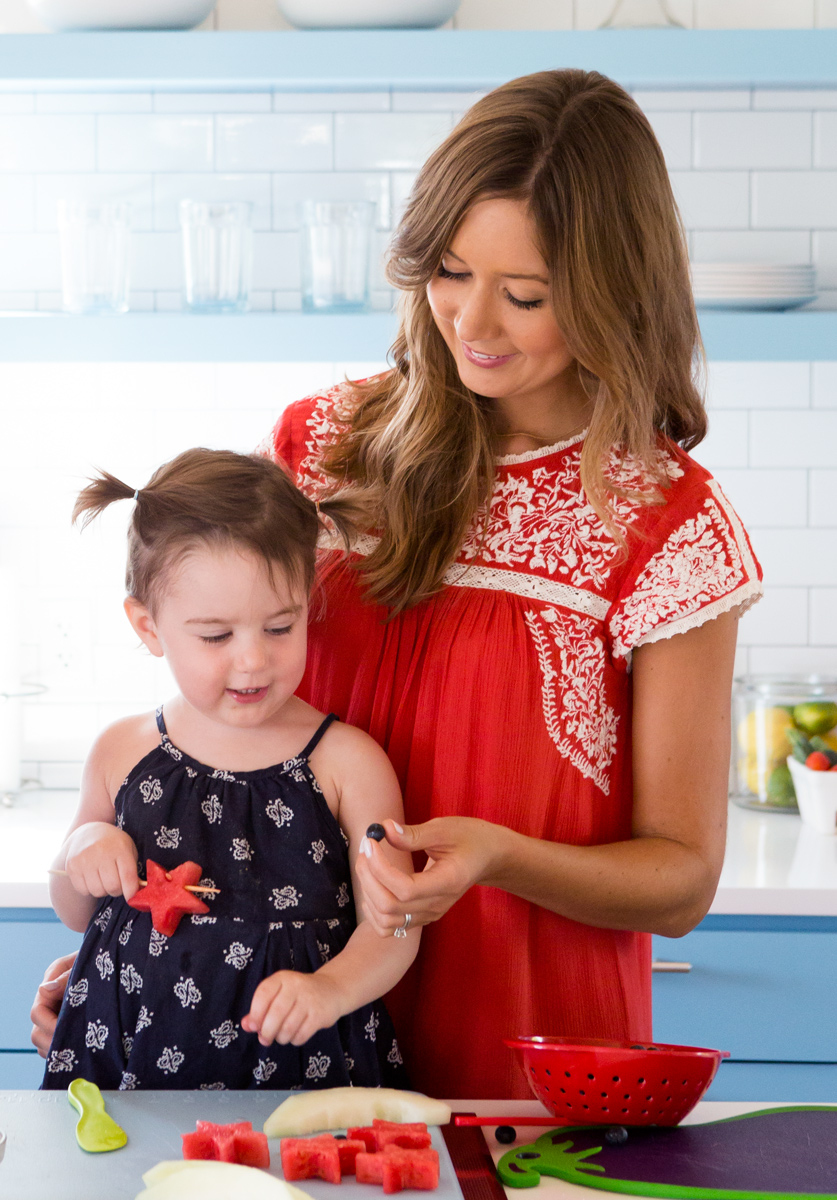 Camille Styles and daughter Pheobe cutting fruit in mexican dress
