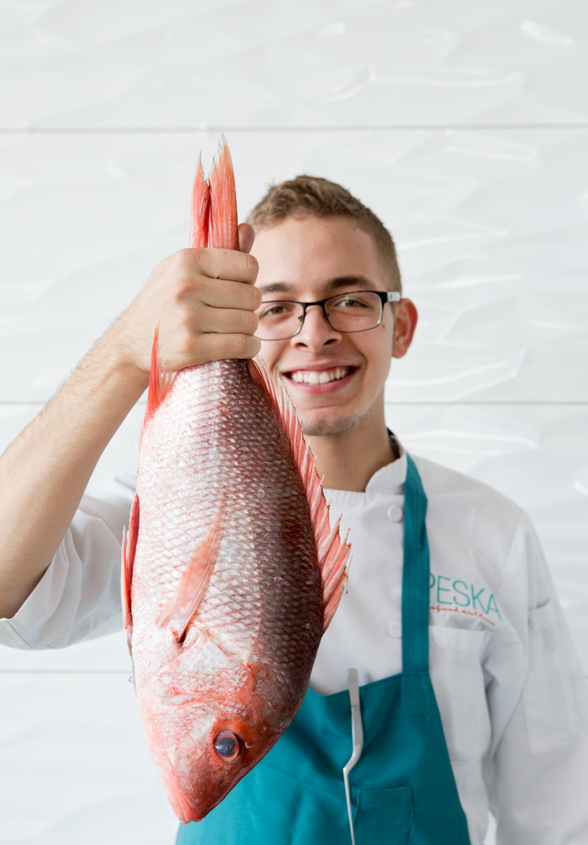 Houston restaurant chef of Peska restaurant holds up fresh red snapper