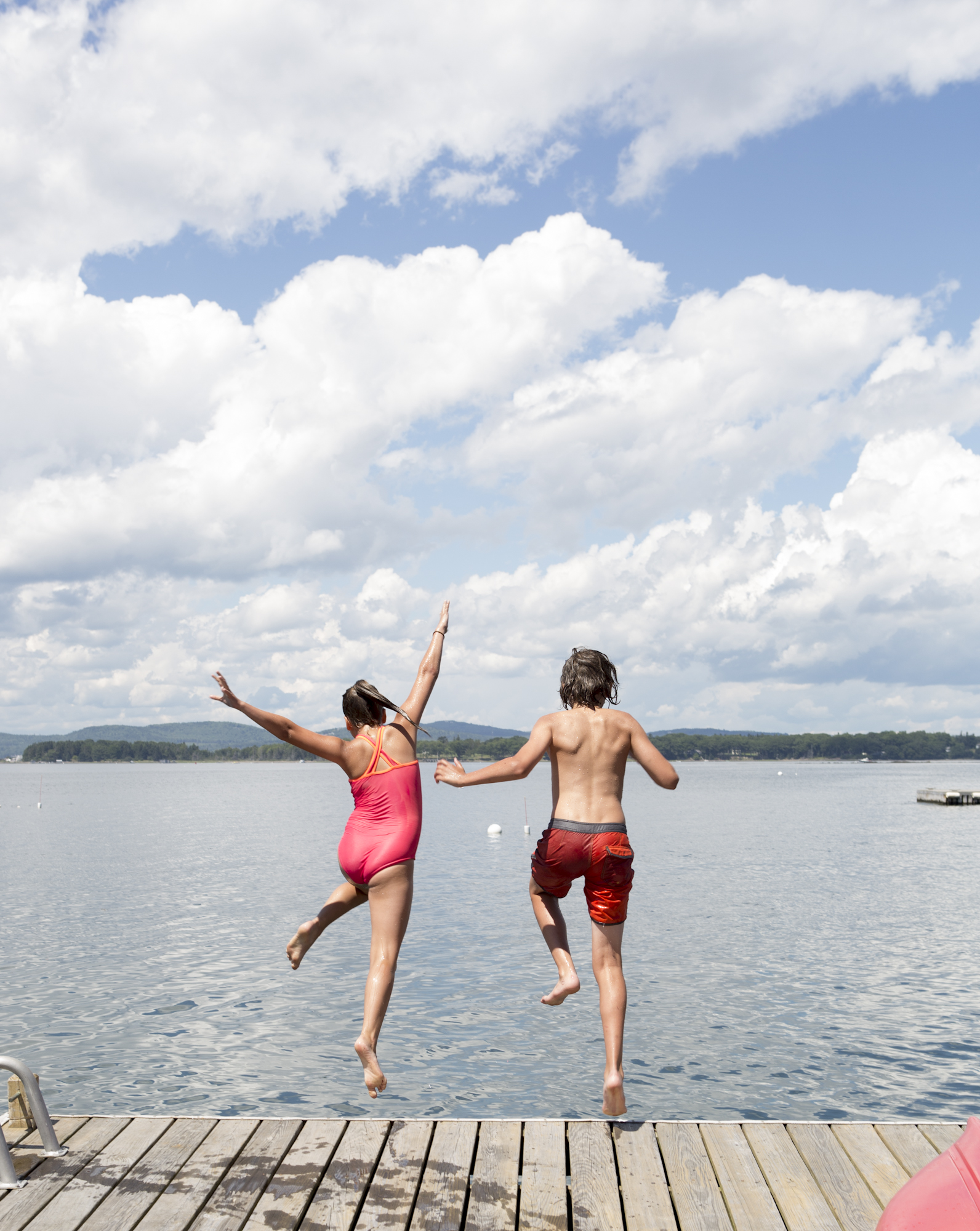Kids jumping off a dock in summer on an island in Isleboro, Maine with brightly colored swimsuits