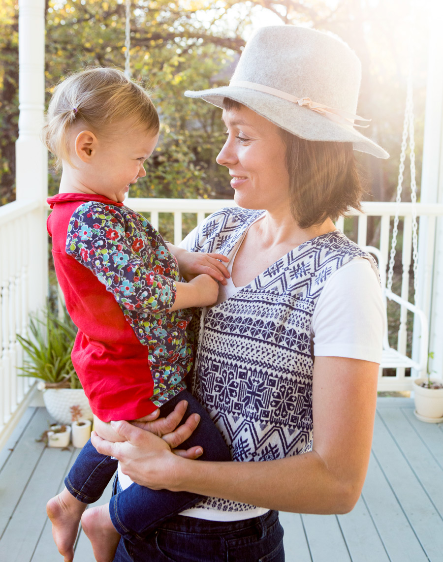 Mom and young daughter laughing on porch with sun steaming in and hat