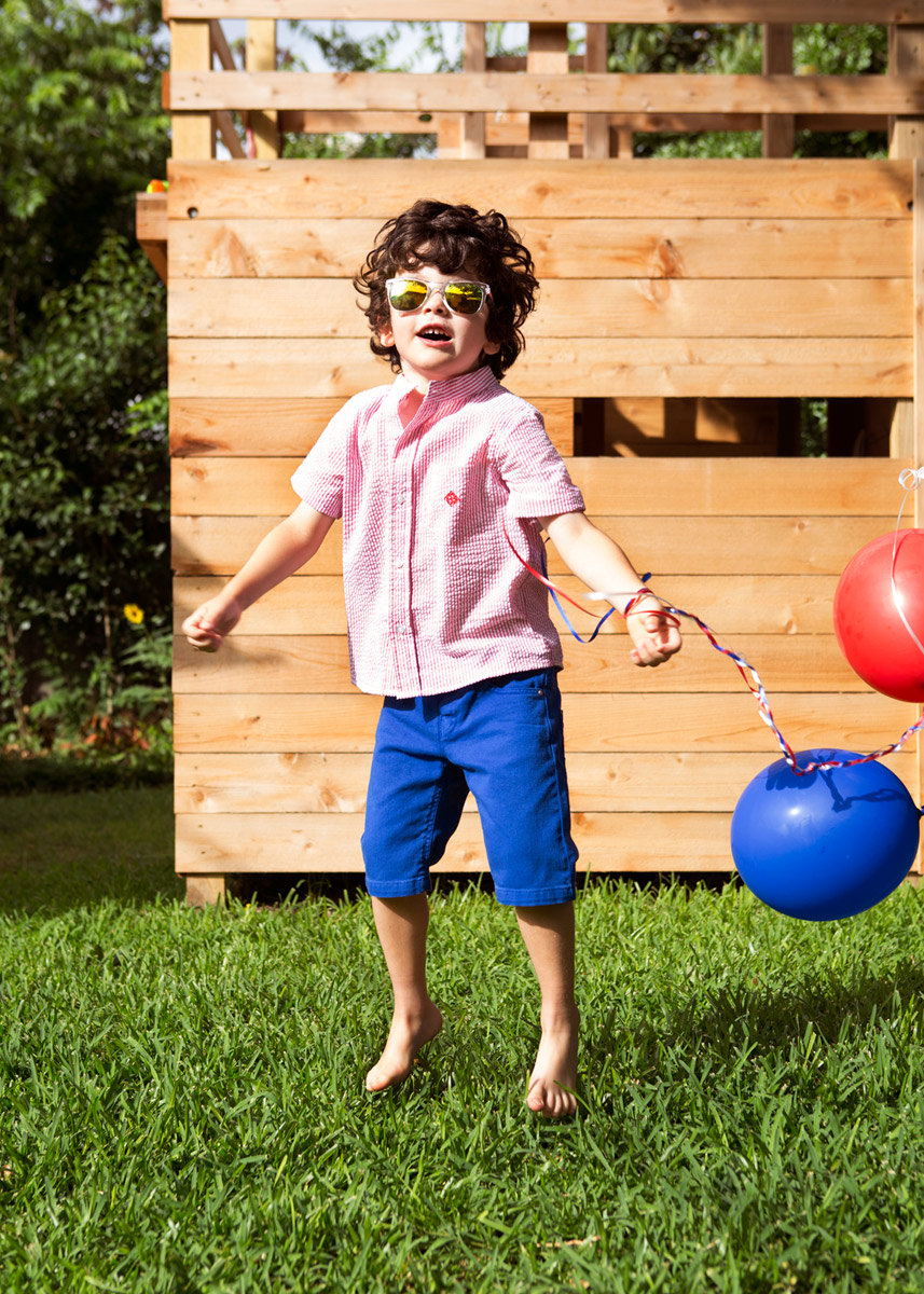 Boy with sunglasses jumping in the air with green grass and wooden fort