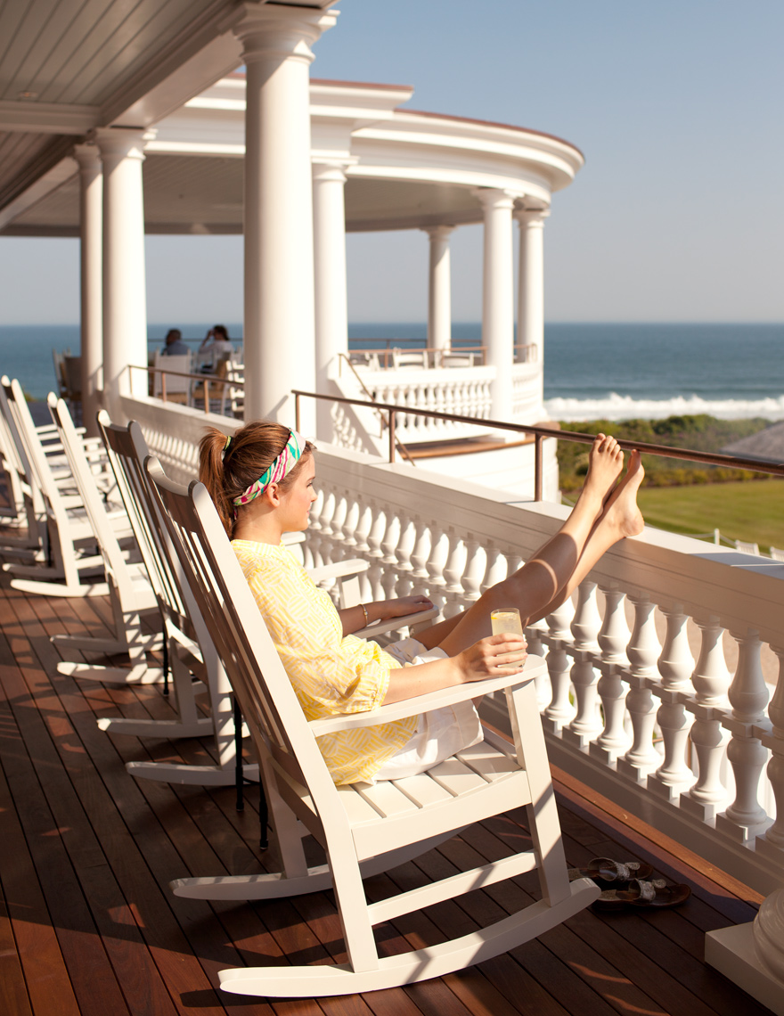 Ocean House girl on rocking chair with lemonade looking at ocean