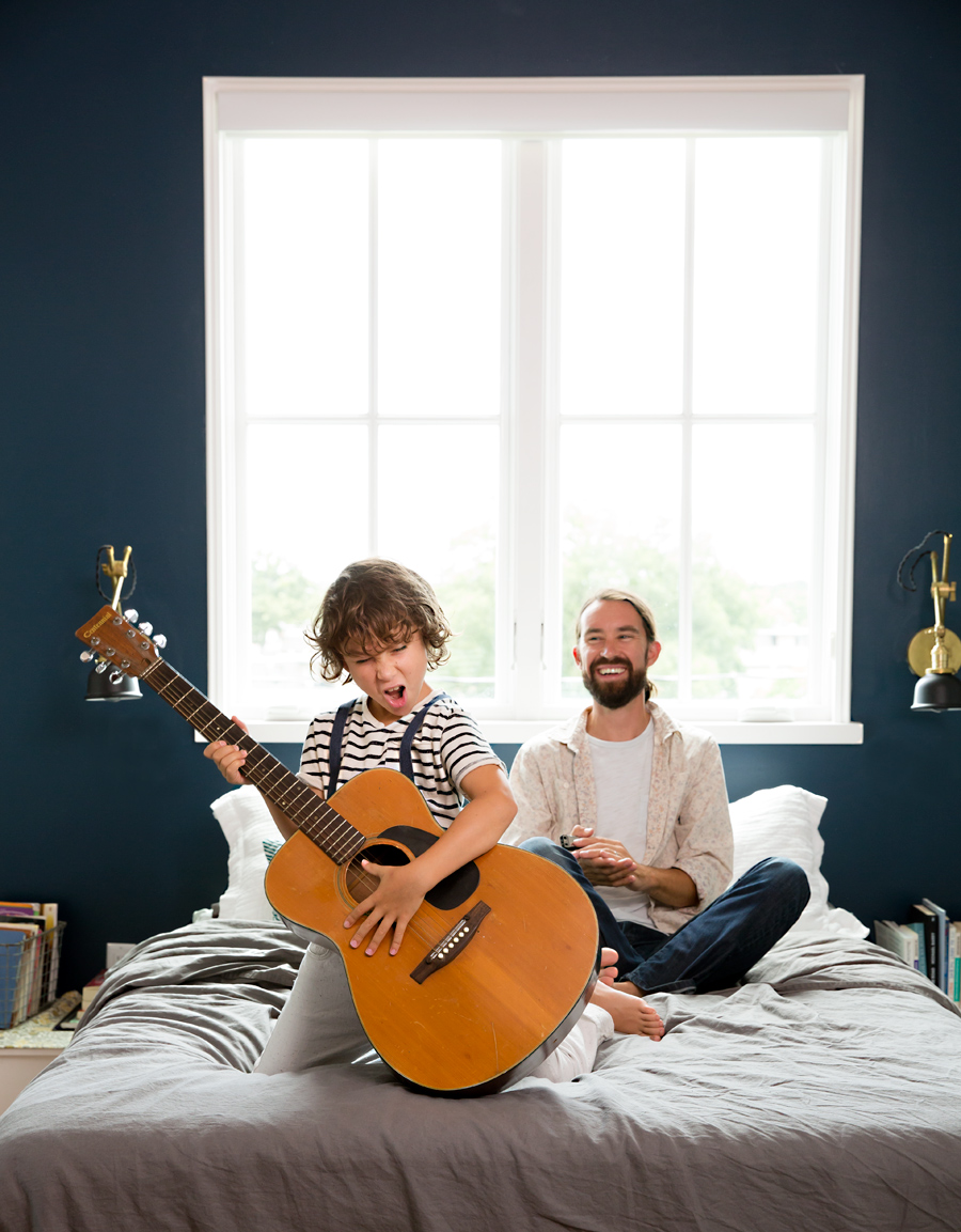 Dad and son at home playing guitar and laughing