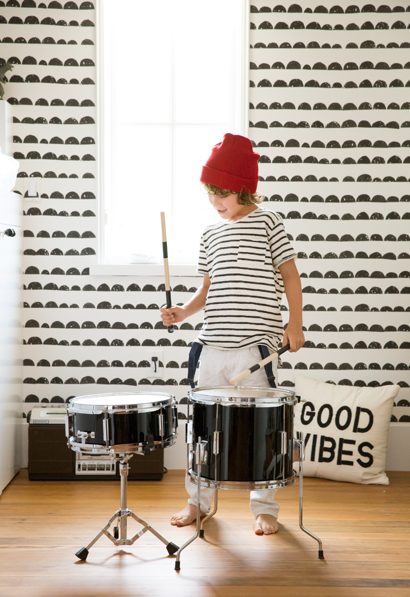 stylish kid playing drums Target pillow and red hat