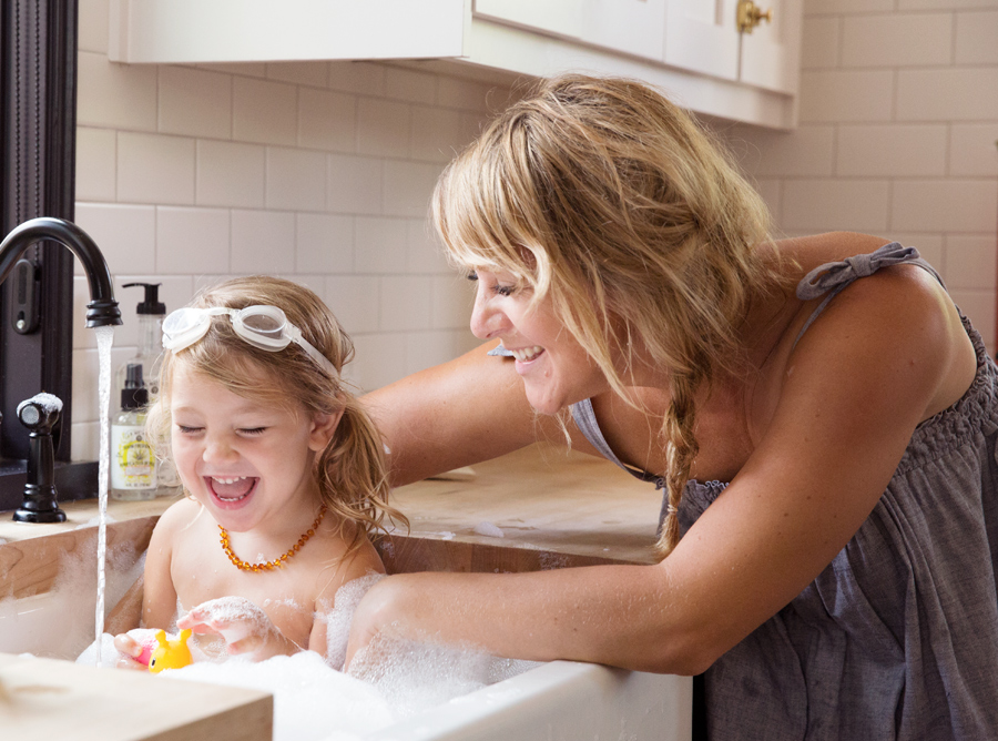Mom and daughter taking bubble bath in sink with goggles