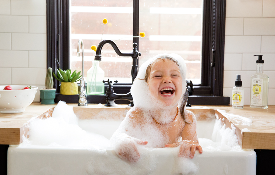 Girl in kitchen sink bathtub laughing