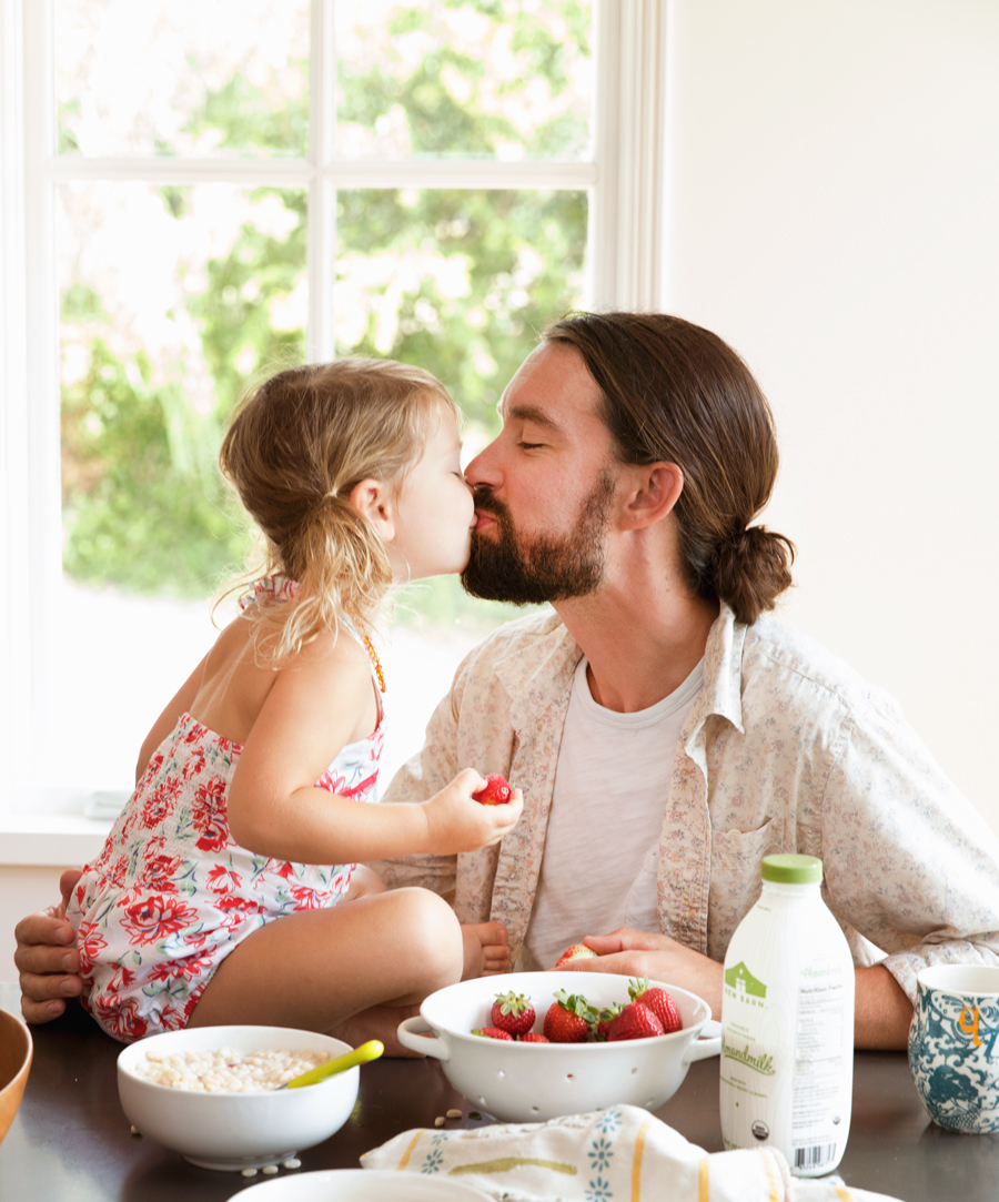 Little girl with Dad eating breakfast of strawberries and cereal on the table.