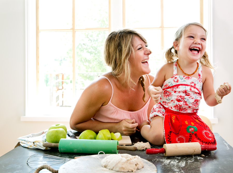Mom and daughter baking together and laughing on a kitchen table