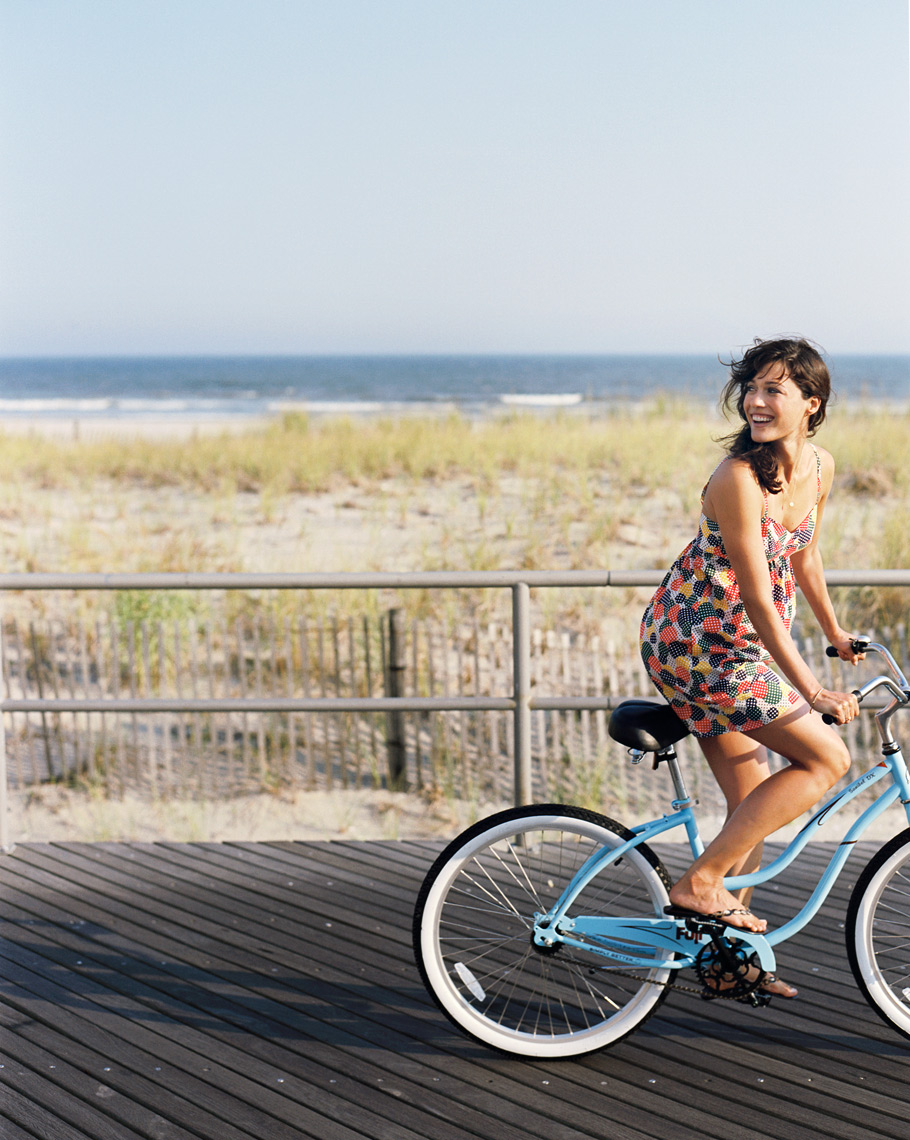 girl riding bike on the jersey shore travel on the boardwalk