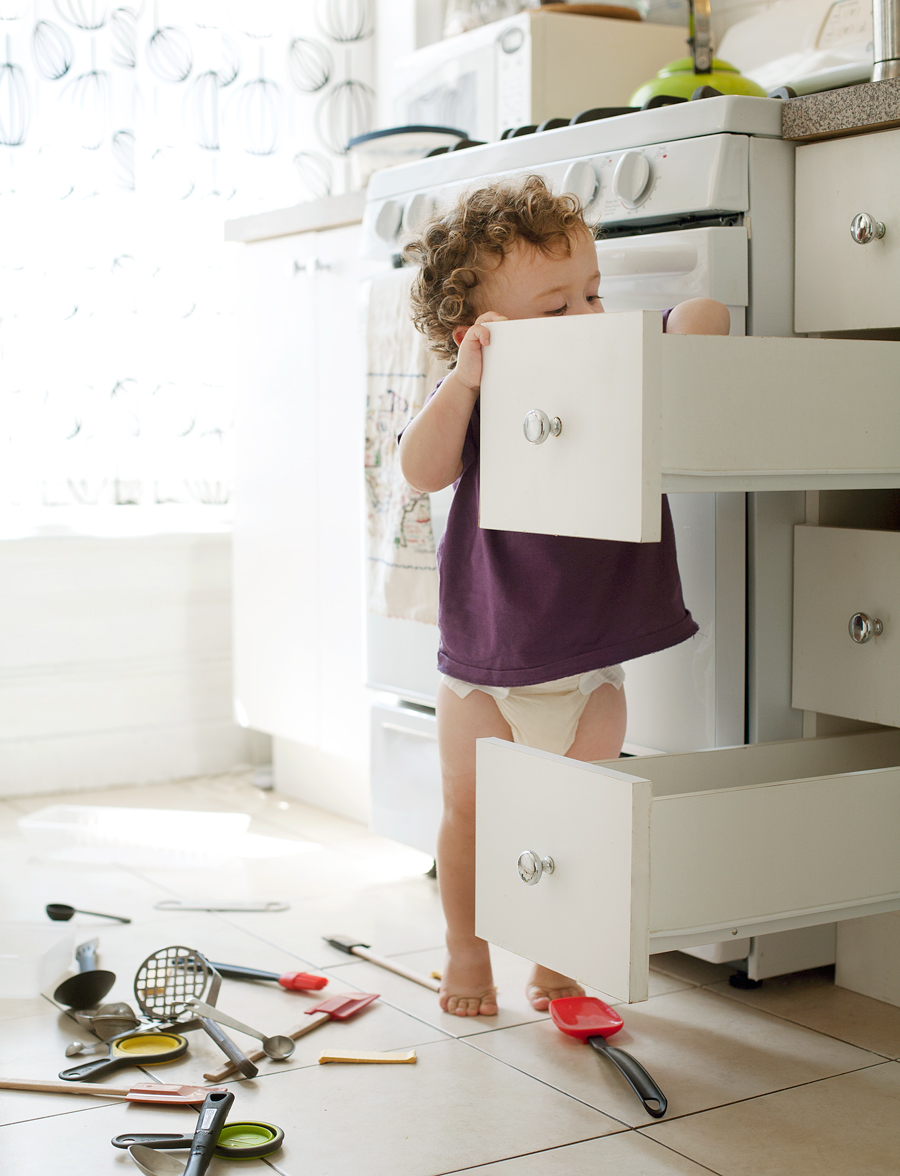 toddler taking stuff out of drawers in kitchen in tip toes