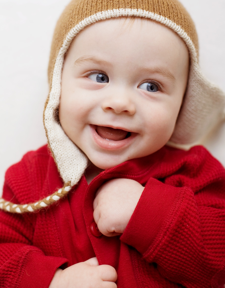 baby in red thermal suit with winter hat and toothless grin