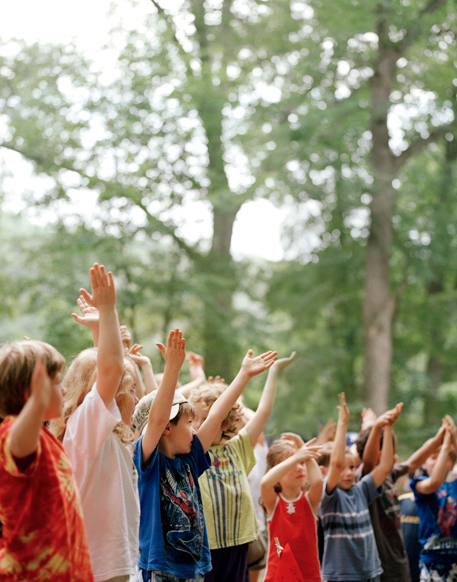 kids in summer camp raising hands in here