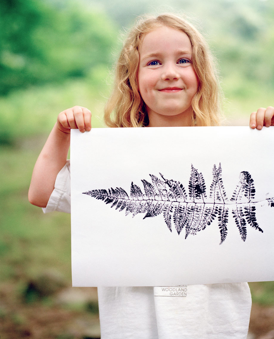 girl holding a leaf print on white paper long blond hair