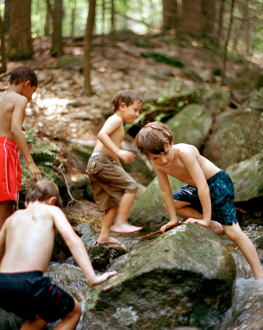 kids playing on rocks in creek in summer