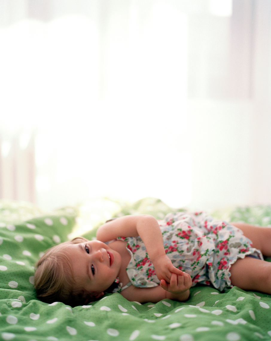 young girl on bed in floral dress laughing